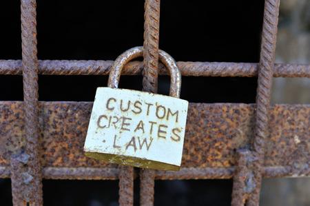 creates: Old padlock with title  custom creates law  on rusty iron grate