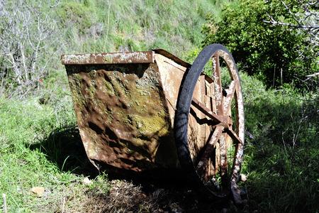 carretilla de mano: Carretilla de mano oxidado viejo en el suelo en el entorno rural.