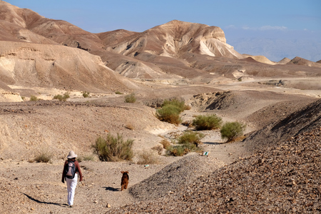 Female hiker with dog on desert trail near Dead Sea in Israel.