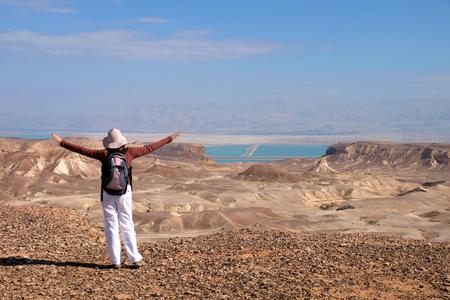 Female hiker standing on desert trail near Dead Sea in Israel. Stock Photo