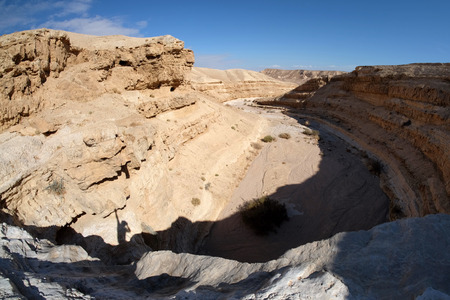 Dry fall and sedimentary rocks in Judea Desert near Dead Sea.