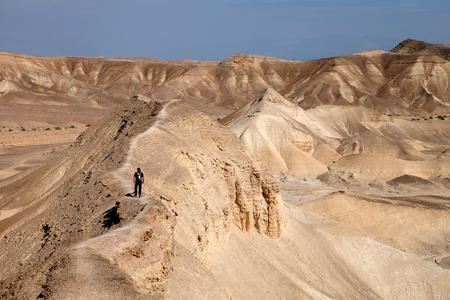 Alone hiker on desert trail near Dead Sea in Israel.