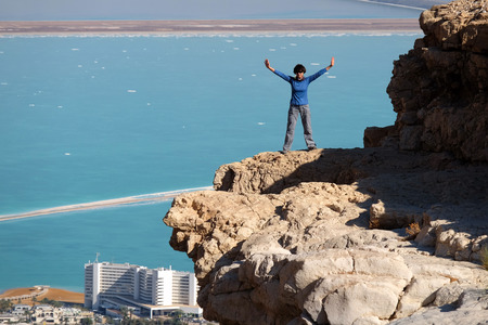 Female hiker standing on rock cliff above Dead Sea, Judea mountains in Israel.
