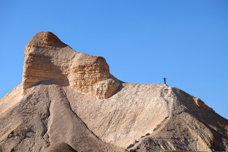 Female hiker standing on mountain ridge in Judea Desert, Israel.
