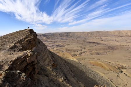 Alone hiker on Big Crater edge in Negev Desert, Israel. Stock Photo