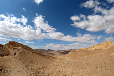 Mountain trekking in desert landscapes with scenic sky and clouds. Stock Photo