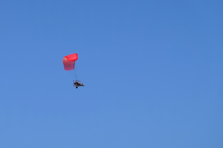 Two men flying in motor paraplan with red wing on blue sky background. Stock Photo