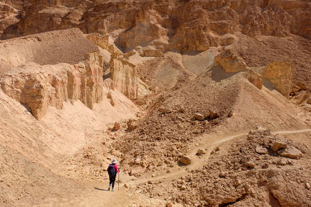 One unrecognized hiker on desert path in Negev mountains, Israel.
