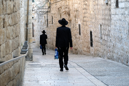 Two unrecognized religious jewish men walking down the street in Old City of Jerusalem. Editorial