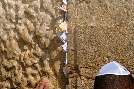 Hand of praying man at the Wailing Wall with notes and wishes, Jerusalem. Stock Photo