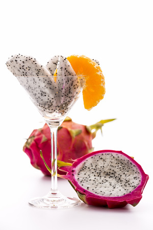Wedges of a pitaya in a glass  Wedges of a pitaya assorted in a glass and decorated with a mandarine slice  Next to it a halved, and behind it, an entire Fruit  photo
