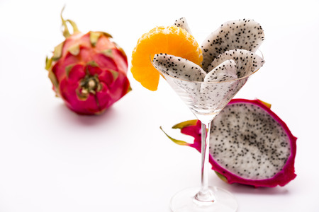 Wedges of the dragon fruit in a glass  Wedges of the dragonfruit assorted in a long-stemmed glass and decorated with a mandarine slice, which also corresponds as regards taste