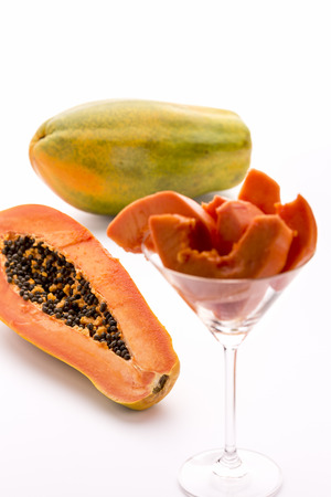 papaw: Papaya - a globose, green and yellow fruit   A halved and an entire papaw fruit  Slices of its fruit flesh arranged in a drinking glass  Stock Photo