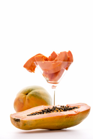 globose fruits: Pawpaw fruit, Carica papaya   A halved pawpaw fruit in focus in the foreground  In the background is an entire fruit and a glass filled with its fruit pulp  Stock Photo