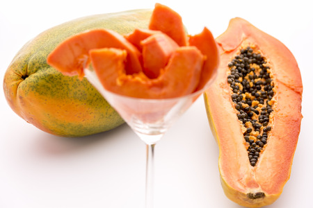 globose fruits: Full of nutrients and papain - the Papaya   Fruit flesh of the papaya arranged in a glass, but the focus rests on the halved papaya and entire fruit in the back