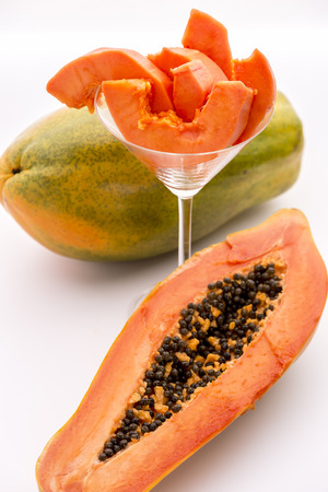halved  half: Papaya - a popular breakfast fruit   The oblong shape of half a papaya and its fruit flesh in a glass  The depth of field is running across both the papaya slices and the pulp revealed by the longitudinal section of the halved fruit  Stock Photo