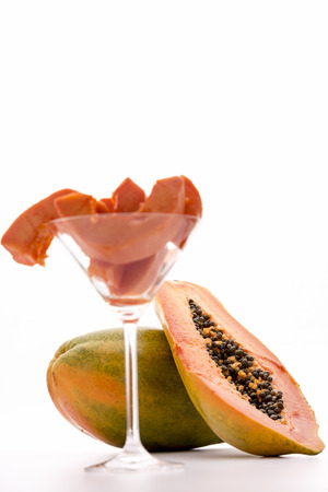 globose: Papaw fruit - succulent pulp and edible seeds   A halved papaya leaning against the globose body of an entire fruit  The ripe pulp has a vibrant tangerine color and numerous black seeds reminiscent of black pepper  Stock Photo