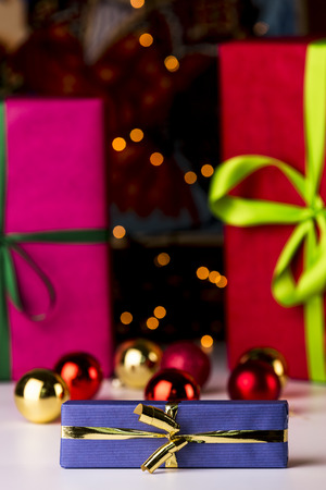 Baubles, twinkles and three wrapped gifts  Christmas bulbs and gifts wrapped in magenta and crimson in soft focus enhancing the sharp outlines of the blue box and golden bow in front  photo