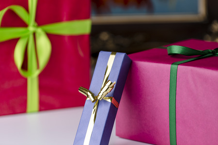 endow: Wrapped gifts  Three gift boxes wrapped in unicolored papers  blue, magenta and purple  Stock Photo