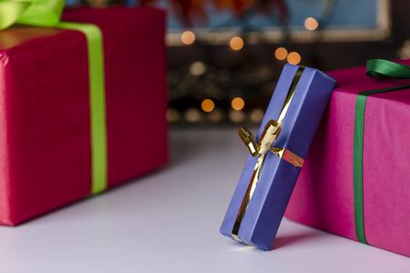 endow: Wrapped presents  Three presents wrapped in blue, red and magenta  Focus is on the golden bowknot, which complements the twinkles in the background