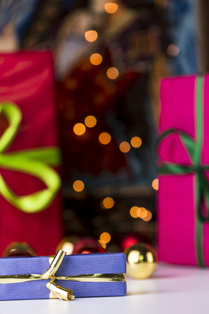 name day: Gifts and twinkles  Solemnly wrapped gifts in unicolored papers  The blue present with the golden bow is within the depth of field  It is in sharp contrast with the red color fields and twinkles in the back