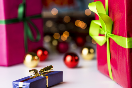 endow: Baubles and gifts  Baubles and glitters in soft focus contrasting with the sharp outlines of the blue wrapped gift in front
