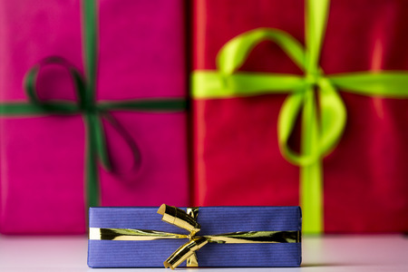 Three bowknots tied around gifts  Magenta and red color-fields of box surfaces in contrast with the shape of green bows  Their soft focus is augmenting the sharp outlines of the golden bowknot and blue wrapping in front  photo