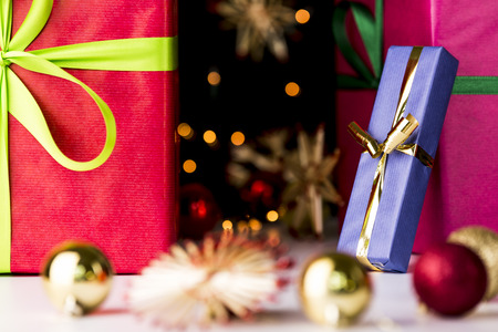 endow: Twinkles, presents, stars and baubles  Sharp outlines of a golden bowknot tied around a blue present accentuating the soft forms of glitters, stars and baubles outside the depth of field  Stock Photo
