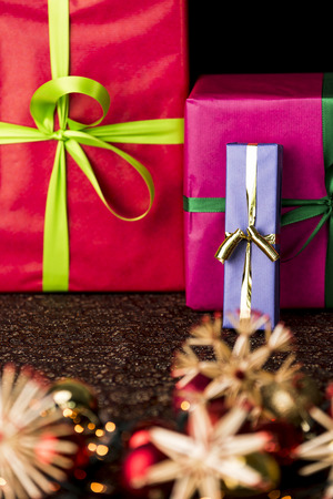 Bowknots, presents, stars and twinkles  Focus on three presents wrapped in blue, magenta and crimson in the background  The sharp outlines of the golden bowknot do counterbalance the hazy shapes of baubles and straw stars  photo