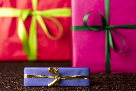 name day: Three presents, bows and ribbons  The golden bow and blue wrapping of a small gift box are in focus and do contrast with the red and magenta color-fields of two larger presents