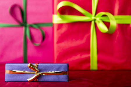 endow: Blue gift with golden bowknot  Two big presents wrapped in crimson and magenta  Their indistinct outlines do contrast with the sharp contours of the small blue gift and golden bow in front  Stock Photo