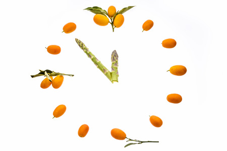 dialplate: It�s almost high noon  A dial-plate shaped out of kumquats with green asparagus tips for clock hands  The time reads five minutes to twelve  All elements are isolated on white  Stock Photo
