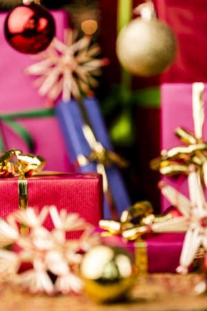 Christmas gifts in vibrant colors between stars and baubles  Focus is on the front plane of the small crimson packet with the golden bow  Atmospheric background with shallow depth of field  photo