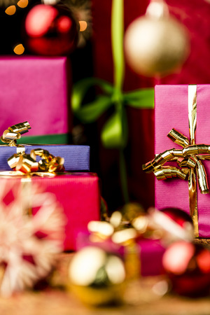 Christmas presents in solid colors between baubles and straw stars  Focus is on the golden bow knot around the magenta box  Seasonal background with shallow depth of field  photo