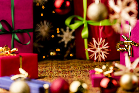 Christmas gifts, glitter balls and straw stars on a festive cloth  Seasonal background with focus on the golden bow tied around the magenta box on the right  Circular composition around a void center  photo