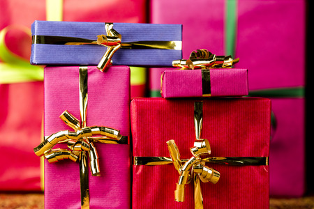 name day: Plain presents in vibrant magenta, crimson and blue wrapping  Flattened space via tight framing  Background for any gift-giving occasion