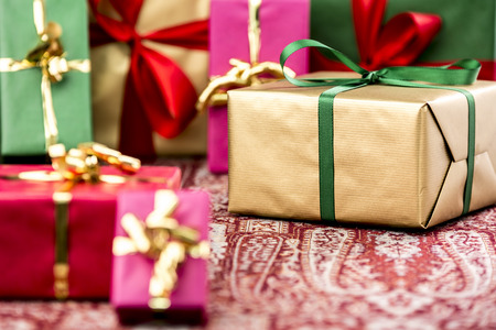 name day: Golden gift box with emerald bow amidst other presents in magenta, red, green and gold. Tightly-framed shot with shallow depth of field. Fit for any gift exchange. Stock Photo