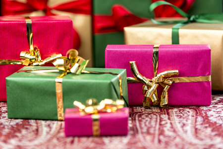 name day: Magenta gift box with golden bow between other plain presents in red, green and gold. Shallow depth of field cuts across the festive cloth. Background for any gift-giving occasion. Stock Photo