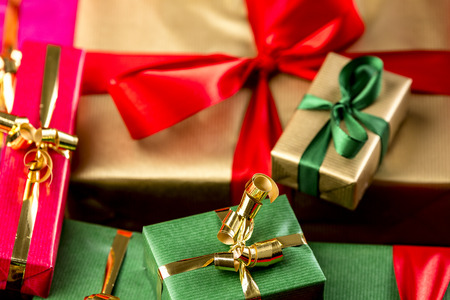 name day: Small golden bowknot around a green gift and large red bow over golden present. Tightly framed. Close-up with shallow depth of field.
