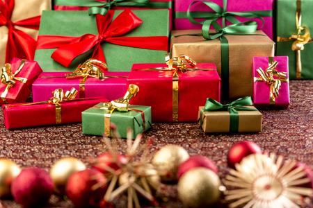 크리스마스 선물 선물을 넘겨 쌓여. 녹색 빨강, 금색, 자홍색으로 싸여 있습니다. 밀 짚 개와 필드의 얕은 깊이 외부 크리스마스 장식품.