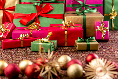 Christmas gifts piled up for handing out of presents. Wrapped in green red, gold and magenta. Straw stars and Xmas ornaments outside the shallow depth of field.  Stock Photo