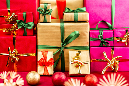 Three piles of plain Xmas presents grouped by color. Red, gold and magenta. All with bow knots. Stars and baubles on red foreground. Shallow depth of field. Vibrant colors. photo