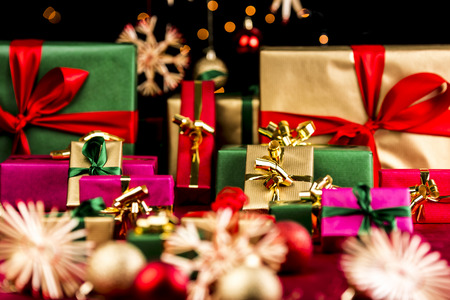 Many plain Christmas presents piled up on a red cloth. All with unicolored bows in red, green and gold. Narrow depth of field resulting in bokeh. Blurred ornaments and stars in front and back.