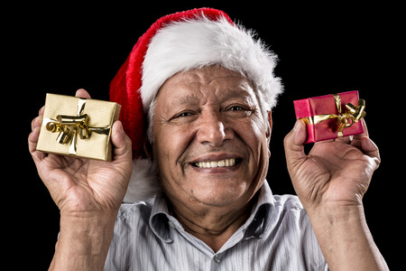 Venerable man brimming over with a smile. He is wearing a Kris Kringle hat. Holding up a small wrapped gift in each hand, golden and red. Christmas theme. Black background. Focus on eyes. Ample DOF. photo