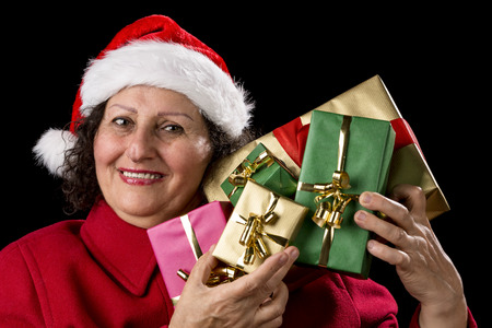 Senior lady with Father Christmas hat is raising five unicolored wrapped Xmas presents to her left cheek Isolated on black background 스톡 콘텐츠
