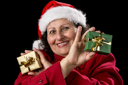 Gentle middle-aged woman with Father Christmas cap and red coat is cracking a smile. She is showing a green and a golden wrapped Xmas present in her hands. Isolated on black photo