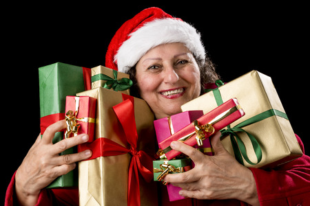 kris kringle: Smiling aged lady with sparkling eyes is embracing eight unicolored wrapped Christmas presents. Santa Claus cap and red coat Isolated on black background Stock Photo