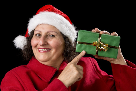 finger bow: Female pensioner with a Father Christmas hat is pointing with her right index finger at a gift in her left hand. The present is wrapped in green and has a golden bow. Isolated over black background.