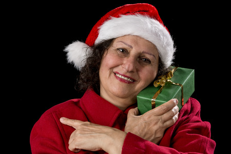 Happy elderly woman with a Santa Claus hat and a red coat. She is holding a green wrapped Christmas present to her left cheek, while pointing with her left index finger to her right. Black background.