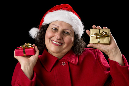 Middle-aged woman wearing a Santa Claus cap. She is cracking a smile while holding a wrapped little Christmas present in each hand. One red, one golden. Isolated on black background 스톡 콘텐츠